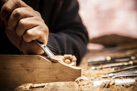 Image of a wood carver using a chisel. Credit: https://www.istockphoto.com/portfolio/PhotoShoppin