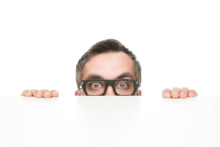 Fearful executive peaking over a desk. Credit: https://www.istockphoto.com/au/portfolio/nastco