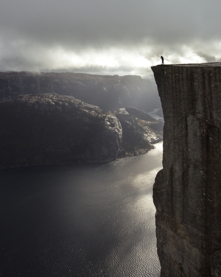 Person standing at a tall cliff face. Credit: Joseph Shelly