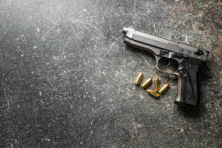A gun with bullets lying next to it. Credit: https://www.istockphoto.com/au/portfolio/jirkaejc