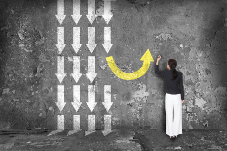 Woman drawing an arrow in a different direction to the others. Credit: https://www.istockphoto.com/au/portfolio/maxsattana